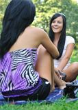 Two friends - women talking outdoors in park royalty free stock photo