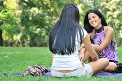 Two friends - women talking outdoors in park Royalty Free Stock Photography