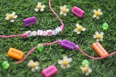 Two friendship bracelet. On grass among flowers and beads Royalty Free Stock Photography