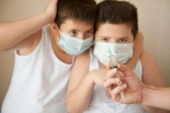Two frightened boys in medical mask looking at hand with syringe stock image