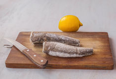 Two frozen carcass of hake and lemon on the cutting board Royalty Free Stock Images