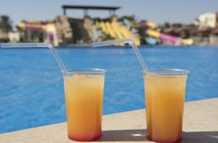 Cocktail drinks by a swimming pool. Two fruit cocktail drinks on bar by a tropical resort swimming pool Royalty Free Stock Photo
