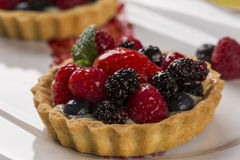 Two Fruit Pies with raspberries, blueberries and mulberries in a. Plate over the table Stock Images