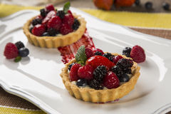 Two Fruit Pies with raspberries, blueberries and mulberries in a. Plate over the table Stock Image