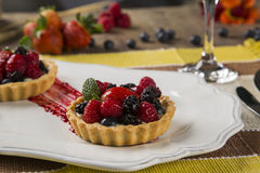 Two Fruit Pies with raspberries, blueberries and mulberries in a. Plate over the table Royalty Free Stock Images