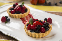 Two Fruit Pies with raspberries, blueberries and mulberries in a. Plate over the table Stock Photography