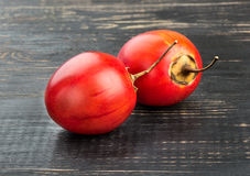 Two fruit tamarillo. Two fresh fruit tamarillo on a dark table Royalty Free Stock Photos
