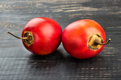 Two fruit tamarillo. Two ripe tamarillo fruit on wooden background Royalty Free Stock Image