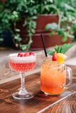 Two alcoholic cocktails garnished with berries and mint. Two fruity alcoholic cocktails garnished with berries and mint on a wooden table outside royalty free stock image