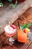 Two alcoholic cocktails garnished with berries and mint. Two fruity alcoholic cocktails garnished with berries and mint on a wooden table outside royalty free stock photography
