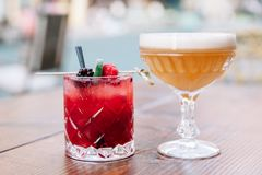Two colorful alcoholic cocktails on a wooden table outdoors. Two fruity alcoholic cocktails garnished with berries and mint on a wooden table outside stock photography