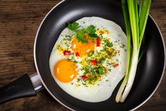 Two frying eggs in pan on table Stock Photo