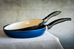 Two frying pans with black pens Stock Photos