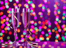 Two full champagne glasses with bokeh lights in the background Stock Photography