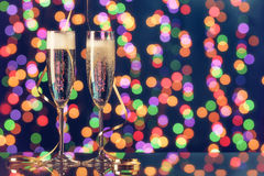 Two full champagne glasses with bokeh lights in the background Stock Photos