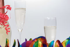 Two full champagne glasses and bottle with colorful garlands. Two full champagne glasses and champagne bottle with colorful garlands Royalty Free Stock Photo