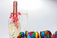 Two full champagne glasses and bottle with colorful garlands. Two full champagne glasses and champagne bottle with colorful garlands Royalty Free Stock Photography