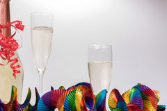Two full champagne glasses and bottle with colorful garlands. Two full champagne glasses and champagne bottle with colorful garlands Royalty Free Stock Photos