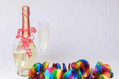 Two full champagne glasses and bottle with colorful garlands. Two full champagne glasses and champagne bottle with colorful garlands Stock Image