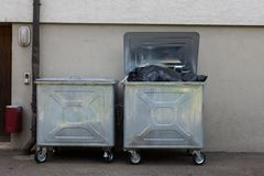 Two full dumpsters. Of trash behind a building Royalty Free Stock Photography