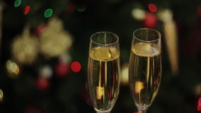 Two full glasses of champagne over color background. Bubbles of champagne in glasses on the background of the Christmas tree stock footage