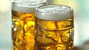 Two full glasses of cold beer. Close-up, visible foam and air bubbles in the glass. Glass of glasses fogged up stock video footage