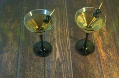Two full martini glasses with two olives on a toothpick stand on a wooden table stock images