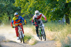 Two Fully Equipped Professional Downhill Cyclists Riding Bikes on the Summer Trail Stock Photos