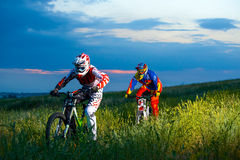 Two Fully Equipped Professional Downhill Cyclists Riding Bikes on the Summer Trail Royalty Free Stock Photo