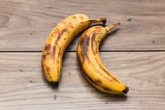 Two fully ripe bananas. On top of a wooden table Stock Photos