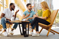 Two fun smart guys explaining their friend something. Just listen. Young intelligent interested lady seeming confused while two guys trying enlightening her on stock images