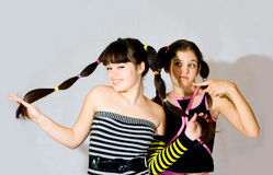 Two fun teen girls. On grey background stock photo