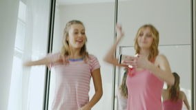 Two fun teen woman dancing in the bedroom. Repeat the dance movements, looking at mobile phone screen. Pajama party stock video footage