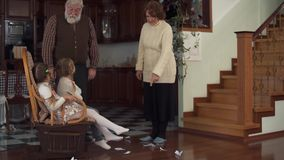 Two funny active granddaughters indulged, and thrown pieces of paper on the floor and their grandparents cursing them. Funny active granddaughters indulged, and stock footage