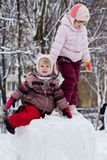 Two funny adorable little sisters building a snowman together in. Beautiful winter royalty free stock photo