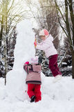 Two funny adorable little sisters building a snowman together in Stock Images