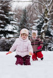 Two funny adorable little sisters building a snowman together in. Beautiful winter park Royalty Free Stock Photo