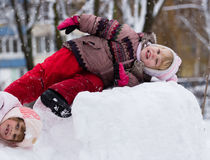 Two funny adorable little sisters building a snowman together in. Beautiful winter park Stock Photo