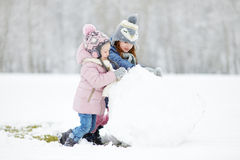 Two funny adorable little sisters in winter park Royalty Free Stock Photos