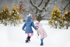 Two funny adorable little sisters winter park Stock Photography