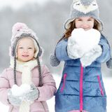 Two funny adorable little sisters winter park Royalty Free Stock Photography