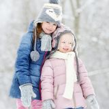 Two funny adorable little sisters winter park Stock Photo