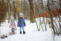 Two funny adorable little sisters winter park Royalty Free Stock Photo