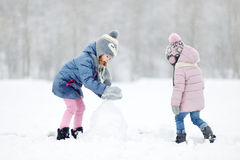 Two funny adorable little sisters in winter park Stock Photo