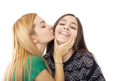 Two funny affectionate teenage friends laughing and kissing Stock Images