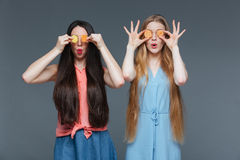 Two funny amazed women covered their eyes with marmalade candies. Two funny amazed cute young women with long hair covered their eyes with marmalade candies over Royalty Free Stock Image