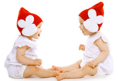 Two funny baby twins in hats. Sitting face to face Royalty Free Stock Images
