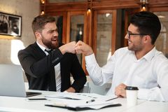 Two funny bearded colleagues in formalwear punched while sitting. At office Stock Images