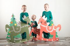 Two funny boys in a Santa Claus hat are playing with horses drawn on cardboard. The guys have fun at home. Christmas holiday conce Royalty Free Stock Image