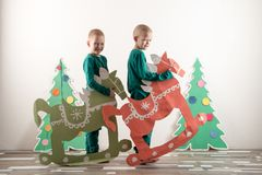 Two funny boys in a Santa Claus hat are playing with horses drawn on cardboard. The guys have fun at home. Christmas holiday conce Royalty Free Stock Photos